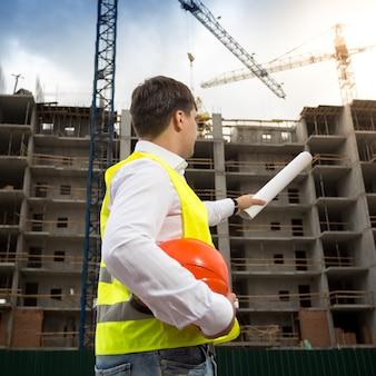 Image vue arrière du jeune ingénieur pointant sur le bâtiment avec des plans roulés