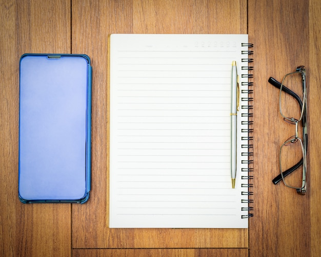 Image vue de dessus du cahier ouvert avec page blanche et téléphone portable sur la table en bois