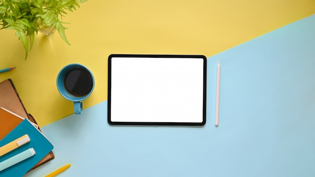 Image vue de dessus de l'espace de travail avec tablette informatique écran plat blanc