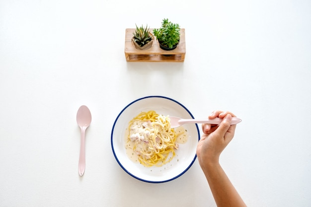 Image vue de dessus d'une femme mangeant des spaghettis à la carbonara sur la table