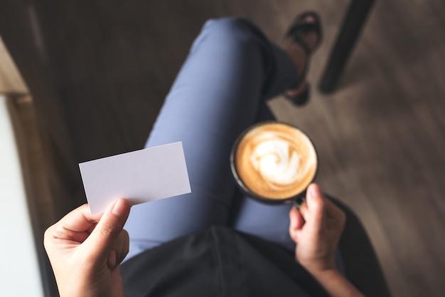 Image vue de dessus d'une femme tenant une carte de visite vide en buvant une tasse de café