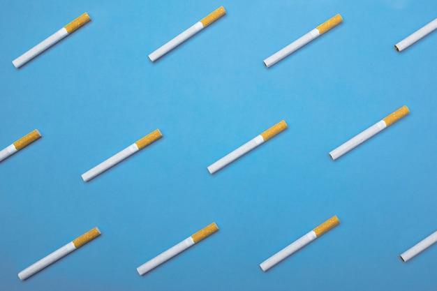 Une image vue de dessus de plusieurs cigarettes sur bleu