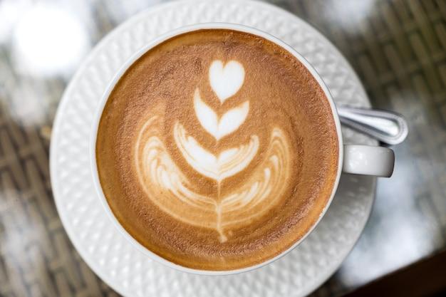 Image vue de dessus d'une tasse de café au lait chaud avec de l'art latte sur table