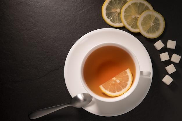 Image vue de dessus d'une tasse de thé au citron sur le mur de granit noir