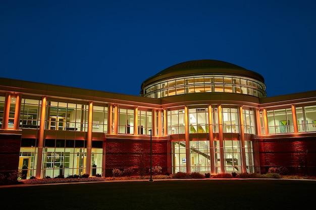 Image de vue de face d'un dortoir d'une université bien éclairé la nuit avec de nombreuses fenêtres
