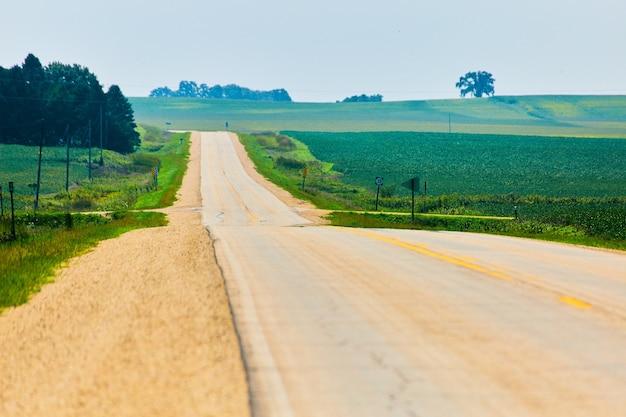 Image de vue latérale de la route menant à des champs verdoyants