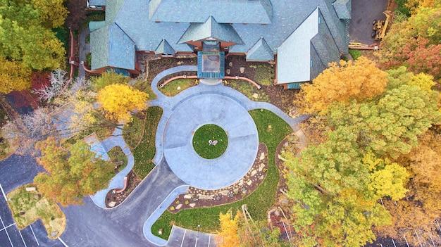Image de vue sur le manoir avec allée circulaire entourée d'arbres forestiers d'automne