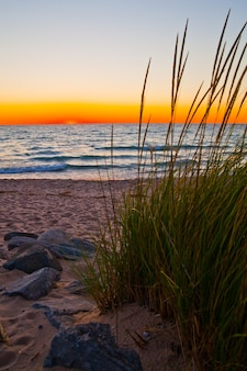 Image d'une vue paisible sur les roseaux des dunes de sable donnant sur un lac au coucher du soleil