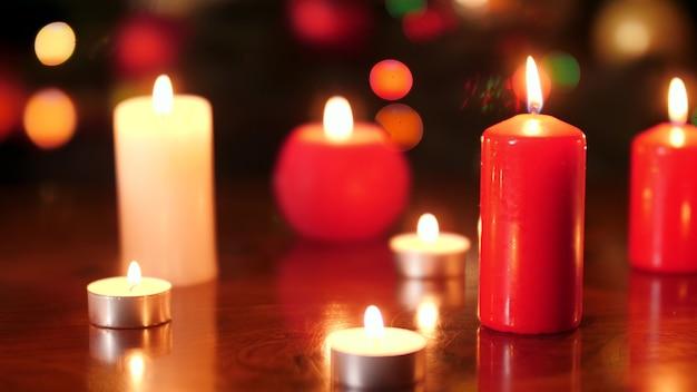 Images 4k de bougies allumées rouges et blanches contre des lumières colorées rougeoyantes la nuit. arrière-plan ou toile de fond parfait pour noël ou le nouvel an