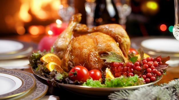 Images 4k de dinde rôtie avec légumes et canneberges dans le salon décorée pour célébrer noël ou le nouvel an. table à manger servie pour la grande famille pendant les vacances d'hiver et les fêtes.