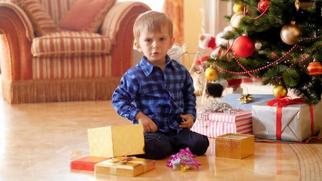 Images 4k d'un garçon bouleversé en colère assis sous l'arbre de noël et criant à cause de cadeaux non désirés et de cadeaux qu'il a commandés au père noël.