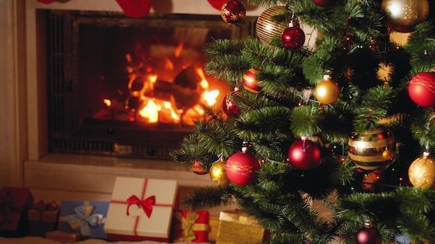 Images 4k de gros tas de cadeaux et de cadeaux à côté d'une cheminée en feu et d'un sapin de noël rougeoyant dans le salon la veille de noël