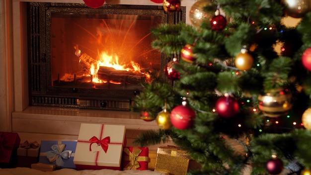Images 4k de nombreux cadeaux et cadeaux de noël sous le sapin de noël à côté d'une cheminée allumée dans le salon