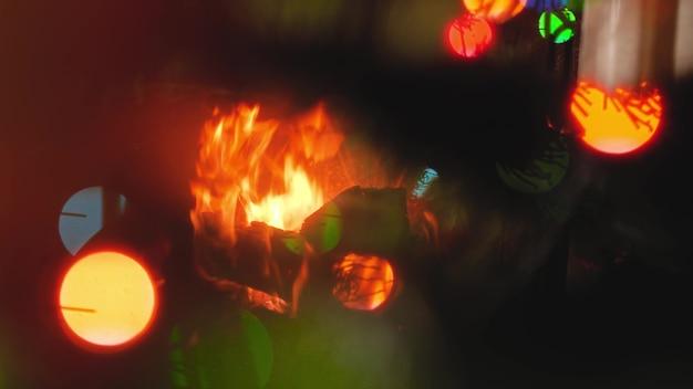 Images abstraites du feu brûlant dans la cheminée, de l'arbre de noël et des lumières colorées rougeoyantes
