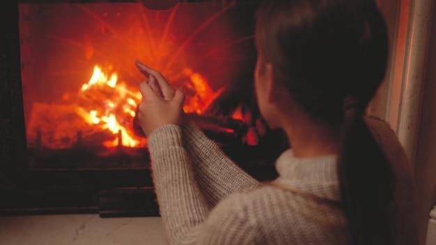 Images aux tons 4k d'une jeune femme assise à côté de la cheminée la nuit et se réchauffant les mains