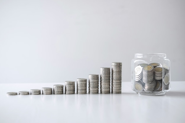Images de croissance empilant des pièces de monnaie et une bouteille de verre (tirelire) pour la planification, une augmentation et des économies