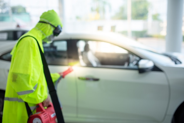 Images floues du spray antiviral covid-19 dans un magasin de voitures ou une salle d'exposition de voitures