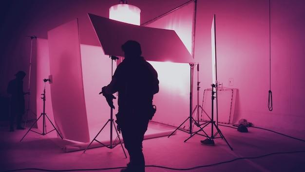 Images floues de l'équipe de production vdo travaillant dans un studio de prise de vue photo avec toile de fond et lumière