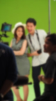 Images floues de la réalisation d'une vidéo commerciale télévisée sur un grand fond d'écran vert. équipe de tournage travaillant avec l'acteur. enregistrement par appareil photo numérique professionnel et kit d'éclairage. filmer les coulisses