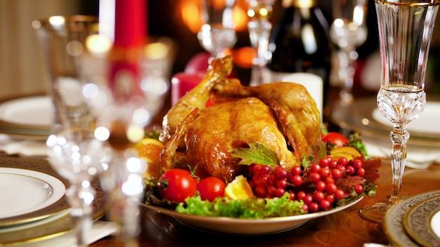 Images de gros plan 4k du dîner de noël avec dinde et champagne contre une cheminée en feu. table à manger servie pour la grande famille pendant les vacances d'hiver et les fêtes.