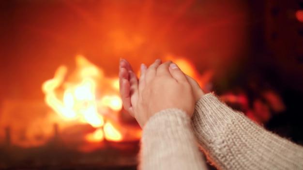 Images de gros plan 4k de jeune femme se frottant les mains et réchauffant le doigt froid près du feu dans la cheminée de la maison
