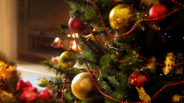 Images de gros plan 4k de lumières led colorées rougeoyantes et clignotantes sur l'arbre de noël contre une cheminée allumée la nuit. photo parfaite pour les fêtes d'hiver et les vacances