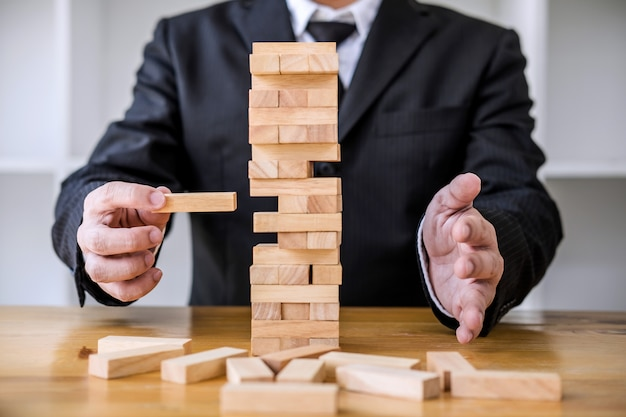 Images de la main de gens d'affaires plaçant et tirant des blocs de bois sur la tour