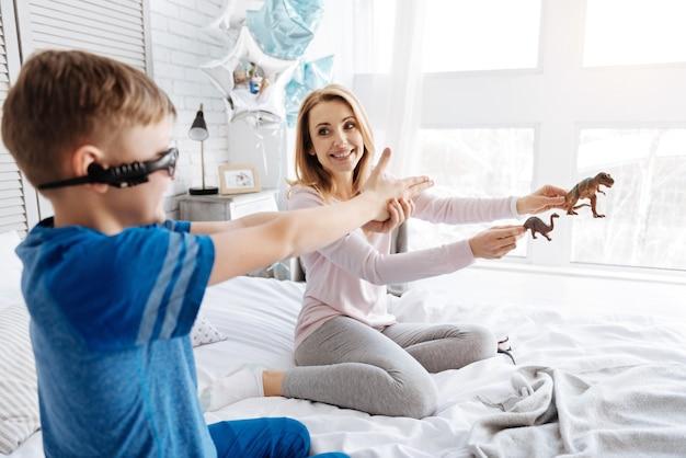 Imagination débordante. ravie belle femme positive souriante et regardant son fils tout en tenant des jouets devant lui