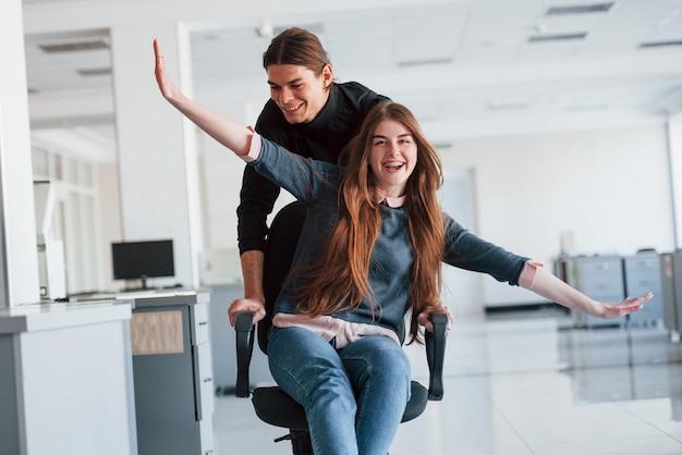 Imaginez que vous êtes l'avion. s'amuser au bureau. les jeunes font une pause et conduisent en utilisant un siège