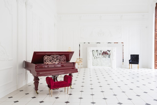 Immense salle blanche de luxe avec un intérieur unique. carrelage noir et blanc au sol, stuc blanc et noir sur les murs, cheminée haute avec mosaïque miroir et piano à queue