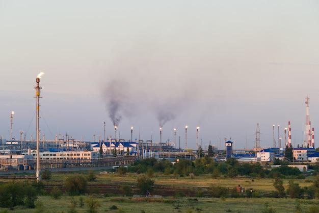 Immense usine de traitement du gaz et du pétrole avec chalumeaux à brûler, tuyaux et distillation du complexe.