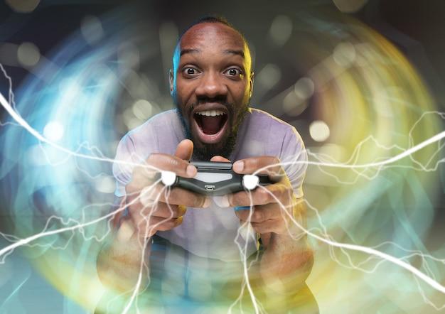 Immersion totale dans le gameplay jeune homme tenant un contrôleur de jeu vidéo isolé sur coloré