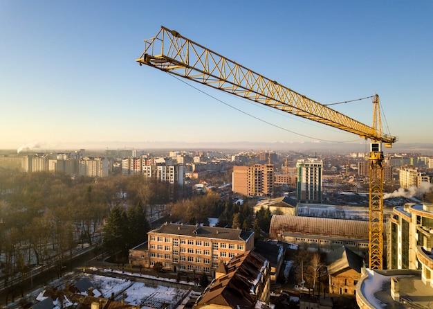 Immeuble d'appartements ou de bureaux en construction, vue de dessus. grue à tour sur fond d'espace de copie de ciel bleu lumineux, paysage de la ville qui s'étend à l'horizon. photographie aérienne de drone.