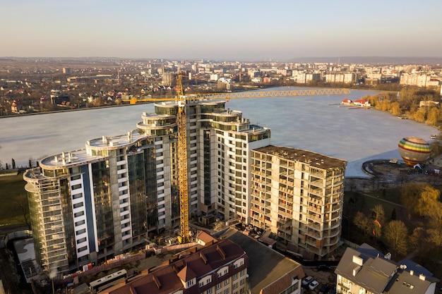 Immeuble d'appartements ou de bureaux en construction, vue de dessus. grue à tour et paysage urbain s'étendant jusqu'à l'horizon. photographie aérienne de drone.