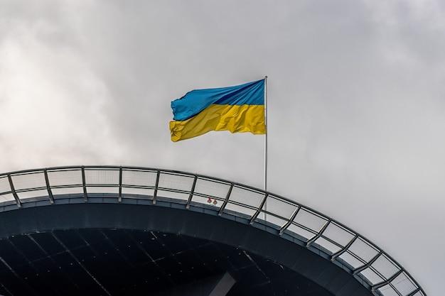 Immeuble de bureaux moderne en verre et acier avec drapeau ukrainien.