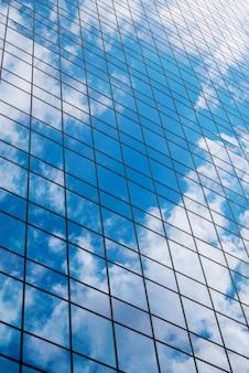 Immeuble de bureaux moderne en verre fumé contre un ciel bleu nuageux