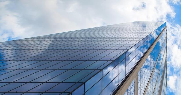 Immeuble de bureaux en verre moderne contre un ciel bleu nuageux