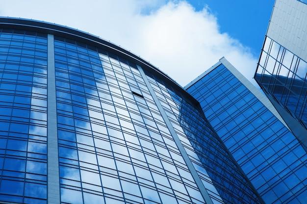 Immeuble de bureaux en verre à plusieurs étages sur fond de ciel.