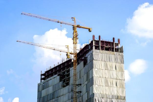 Immeuble en construction avec des grues de levage sur ciel bleu et nuageux.