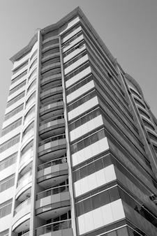 Immeuble gratte-ciel avec balcons, en noir et blanc.
