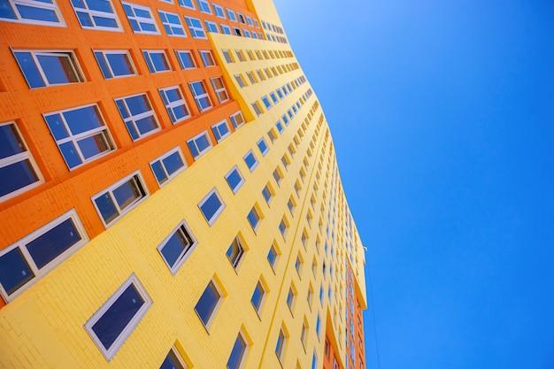 Immeuble à plusieurs étages avec de nombreuses fenêtres en verre debout sur fond de ciel bleu. bâtiments résidentiels, immobilier urbain photo stock