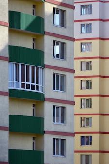 Immeuble résidentiel récent ou récemment achevé sur plusieurs étages avec fenêtres et balcons.