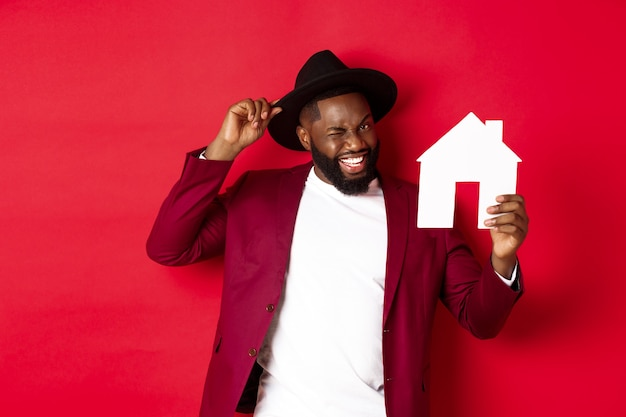 Immobilier. enthousiaste homme noir montrant la maison de papier et souriant