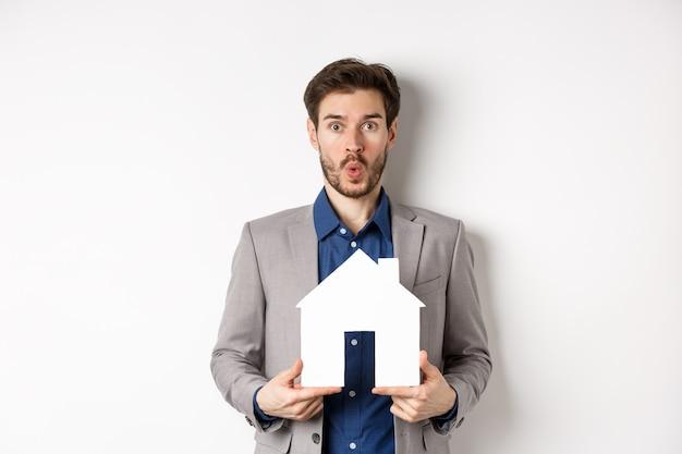Immobilier. homme caucasien étonné en costume vérifiant l'offre spéciale pour la propriété