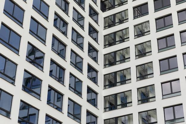 Immobilier neuf à vendre, façade d'appartement avec grandes fenêtres noires et reflet du ciel.