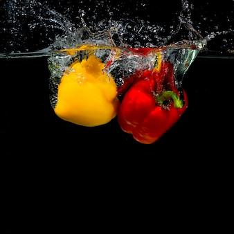 Impact du poivron tombant dans l'eau sur fond noir