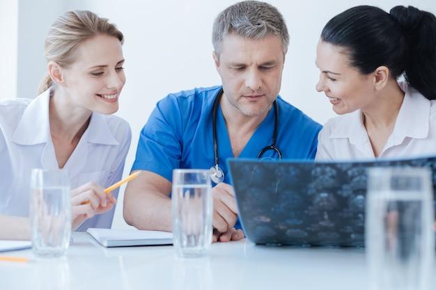 Impliqué des neurologues qualifiés expérimentés travaillant et discutant du scanner cérébral tout en partageant des points de vue