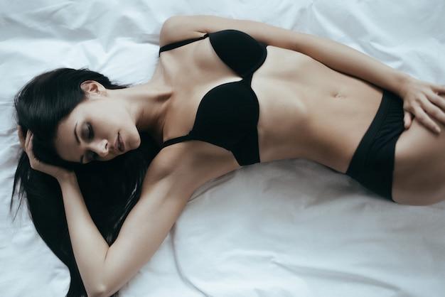 Impossible de lui résister. vue de dessus de la magnifique jeune femme en lingerie noire posant de manière séduisante