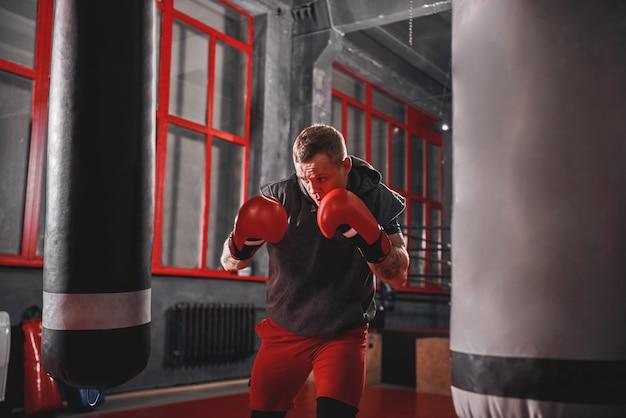 Impossible n'est rien sportif musclé en vêtements de sport s'exerçant sur un sac de frappe lourd avant