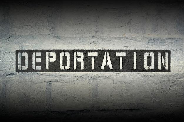 Impression de pochoir de déportation sur le mur de briques blanches grunge